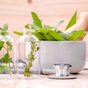50956181 - alternative health care fresh herbal in laboratory glassware  with  stethoscope on wooden background.