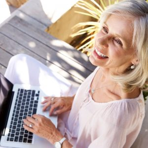 74022214 - close up portrait of happy older woman with laptop computer sitting outside