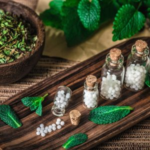Homeopathic globules in small bottles with mint leaves in background, homeopathy concept