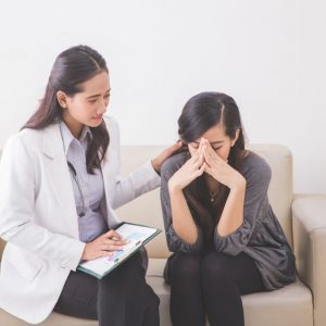 A portrait of Asian female patient crying while consulting her health problem with a female doctor